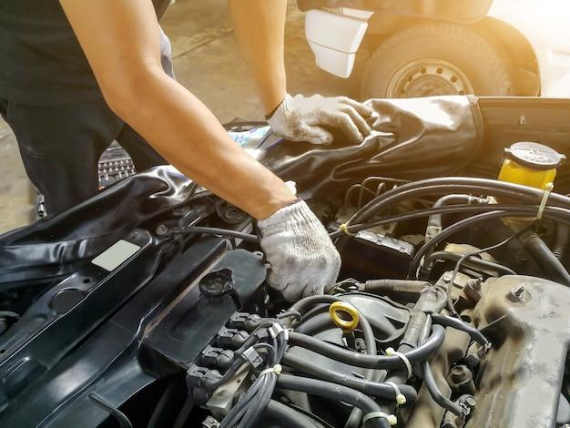 Automechaniker mit werkzeugfunktion prüfen und einen alten automotor an der tankstelle reparieren, vor der fahrt wechseln und reparieren Premium Fotos