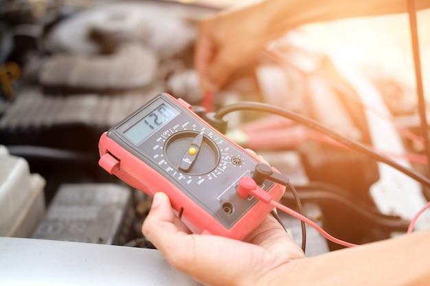 Automechaniker überprüfen autobatteriespannung durch voltmeter-multimeter Premium Fotos