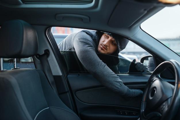 Autoräuber öffnet tür, riskiert job, stiehlt. männlicher bandit mit kapuze steigt beim parken in das fahrzeug ein. autodiebstahl, autokriminalität Premium Fotos