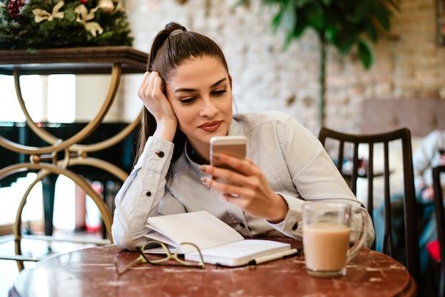Autorin, die telefon beim trinken des kaffees und schreiben von anmerkungen verwendet. Premium Fotos