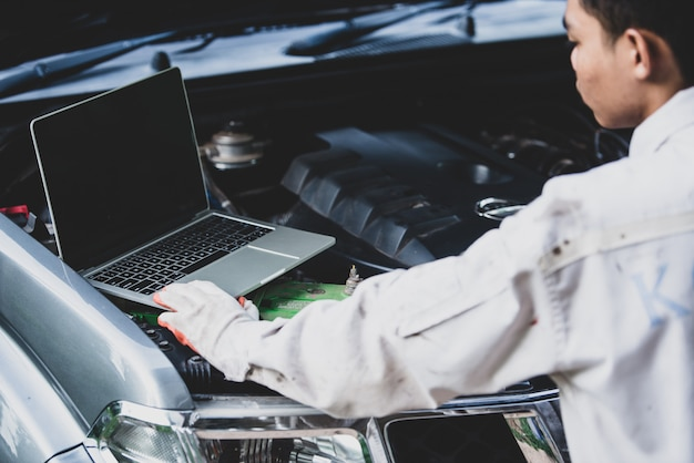 Autoschlosser, der eine weiße uniform steht und hält einen schlüssel trägt, der ein wesentliches werkzeug für einen mechaniker mit laptop maschine überprüfend ist Kostenlose Fotos