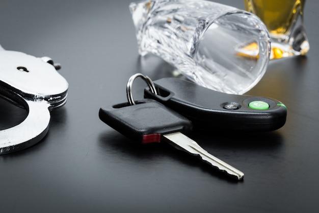 Autoschlüssel auf der bar mit verschüttetem alkohol Premium Fotos