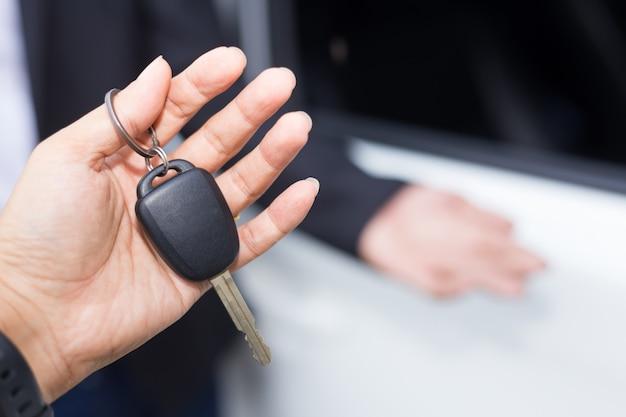 Autoverkäufer, der den schlüssel übergibt Premium Fotos