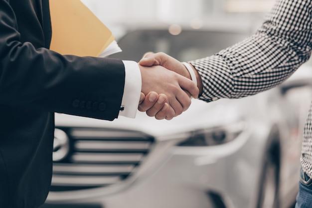 Autoverkäufer, der mit einem kunden an der verkaufsstelle arbeitet Premium Fotos