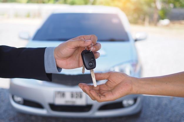 Autoverkäufer senden schlüssel an neue autobesitzer. gebrauchtwagenverkaufsagentur, autovermietung Premium Fotos
