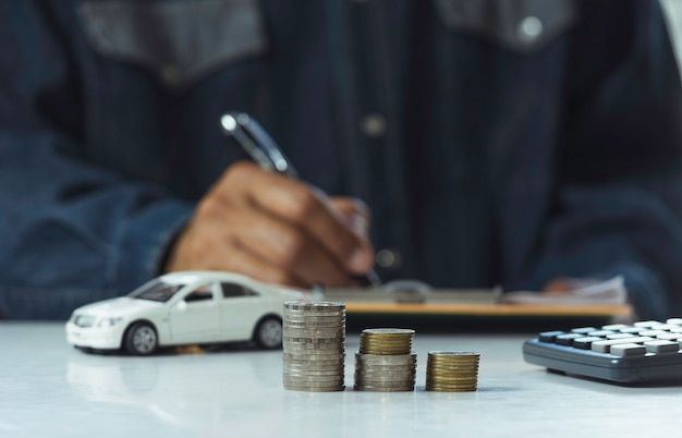 Autoversicherung und autoservice, geschäftsmann mit stapel münzen und spielzeugauto Premium Fotos