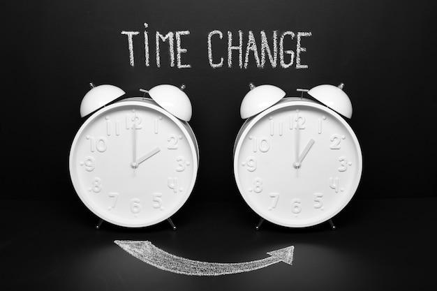 Autumn time change fallback-konzept. zwei vintage-uhren mit kreidetext auf tafel Premium Fotos