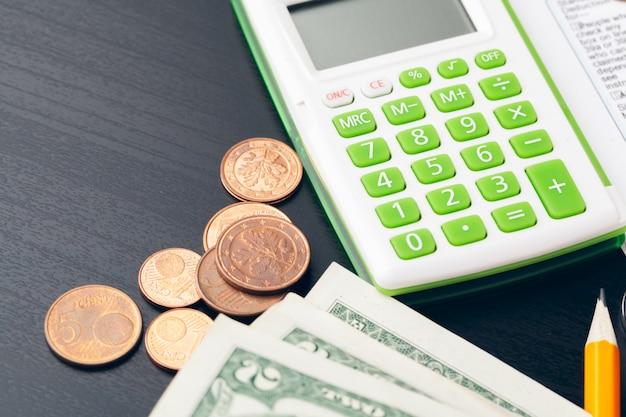 Avings, finanzen, wirtschaft und hauptkonzept - nah oben vom taschenrechner, der geld zählt und zu hause anmerkungen macht Premium Fotos