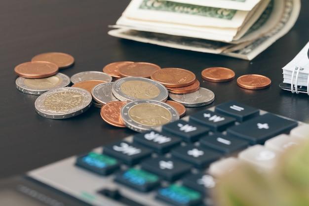 Avings, finanzen, wirtschaft und haus - nah oben vom taschenrechner, der geld zählt und zu hause anmerkungen macht Premium Fotos