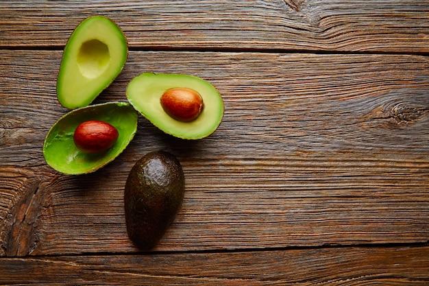 Avocado geschnitten auf gealterte hölzerne tischplatte Premium Fotos