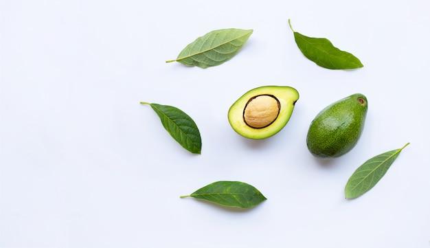 Avocado mit grünen blättern auf einem weiß Premium Fotos