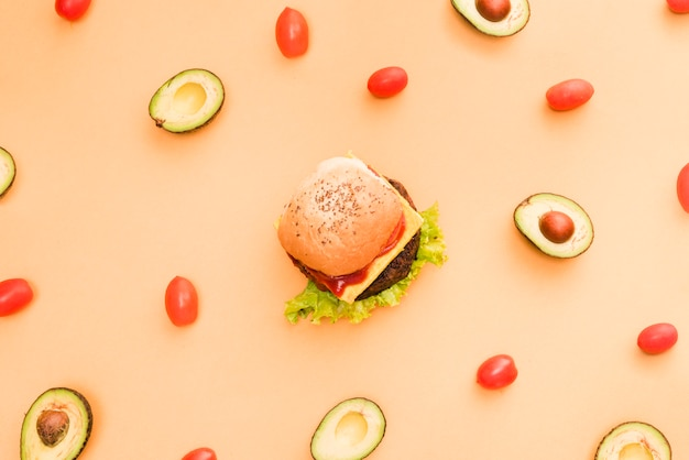 Avocado- und kirschtomaten umgeben um den hamburger auf farbigem hintergrund Kostenlose Fotos