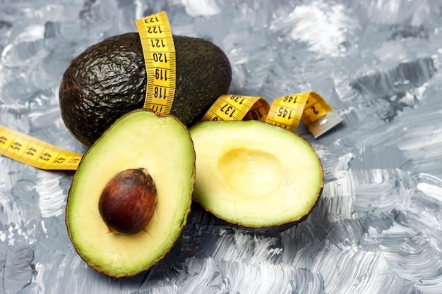 Avocado und maßband auf grau Premium Fotos
