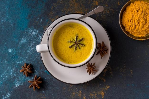 Ayurvedic goldene gelbwurz latte-milch gemacht mit gelbwurz und anderen gewürzen auf blauer tabelle Premium Fotos