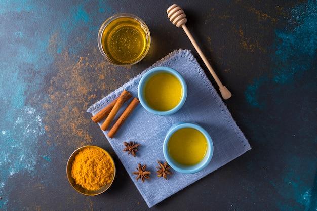 Ayurvedische goldene kurkuma latte milch mit kurkuma und anderen gewürzen blau Premium Fotos