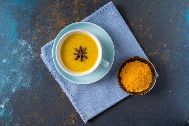 Ayurvedischer goldener kurkuma-latte-milchtee, der mit kurkuma und anderen gewürzen auf blauem hintergrund gemacht wird. flach liegen. Premium Fotos
