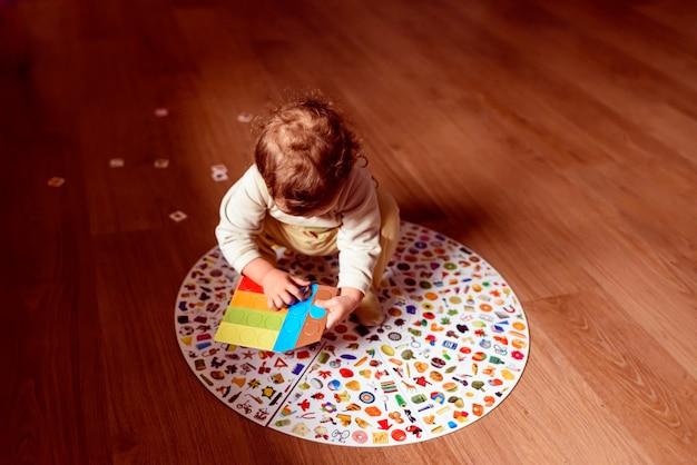 Baby auf dem boden seines hauses, das mit einem traditionellen spiel spielt. Premium Fotos