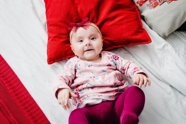 Baby, das auf bett mit kissen im schlafzimmer liegt. fröhliche weihnachten. draufsicht, flatlay. das konzept des familienurlaubs. nahansicht. Premium Fotos