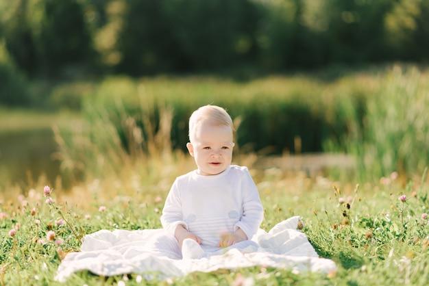 Baby, das auf einem plaid auf natur in einem hellen bodysuit sitzt Premium Fotos