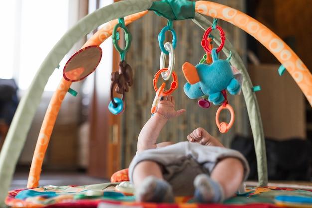 Baby, das auf sich entwickelnder wolldecke mit beweglichen pädagogischen spielwaren liegt Kostenlose Fotos