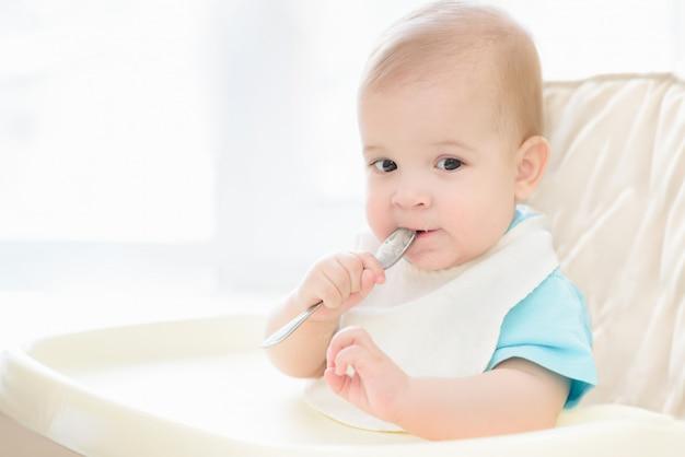 Baby, das einen löffel in seinem mund hält Premium Fotos