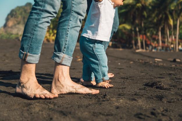 Baby, das erste schritte mit eltern am sandstrand macht Kostenlose Fotos