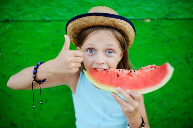 Baby, das gierig reife wassermelone auf einem grünen hintergrund isst Premium Fotos