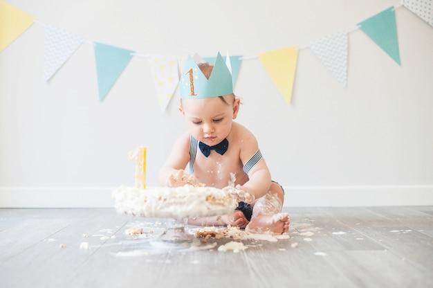 Baby, das mit einem kuchen während seiner zertrümmernkuchen-geburtstagsfeier spielt Premium Fotos