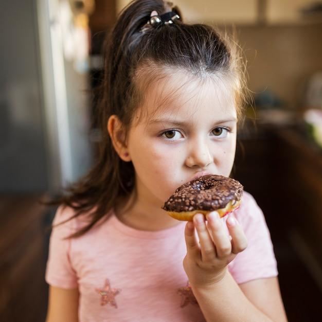 Baby, das schokoladendoghnout isst Kostenlose Fotos