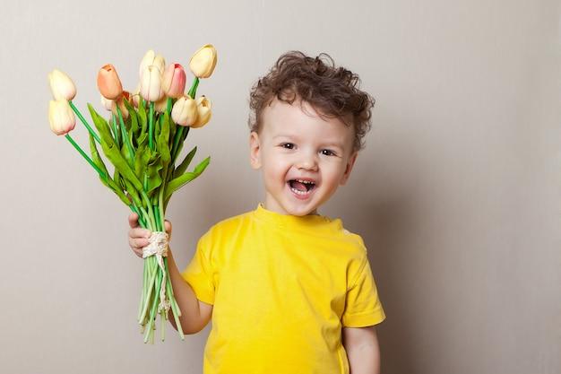 Baby, das unter rosa tulpen lacht Premium Fotos