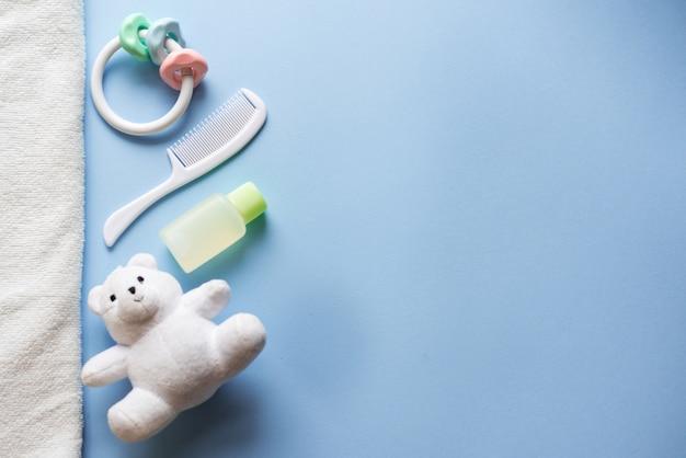 Baby-dusche lag flach auf blau. kinderspielzeug und shampoo. Premium Fotos