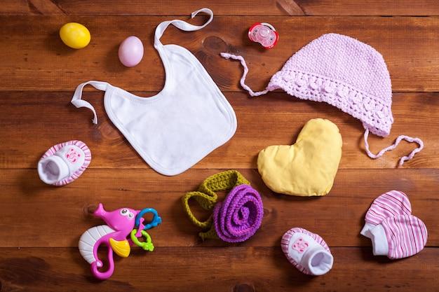 Baby gestrickte kleidung auf braunem holztisch, draufsicht flach gelegt Premium Fotos