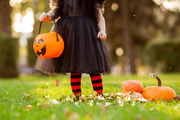 Baby hält ein kürbisförmiges café für halloween, nahaufnahme, platz für text Premium Fotos