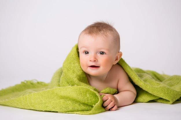 Baby im grünen plaid auf weiß Premium Fotos
