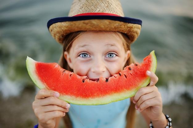 Baby im hut isst eifrig saftige wassermelone auf seehintergrund Premium Fotos