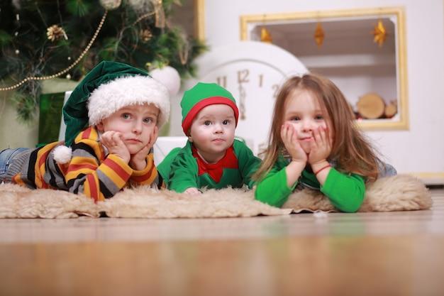 Baby im rotgrünen elfenkostüm mit seinem älteren bruder und seiner schwester in den weihnachtsmützen, die unter weihnachtsbaum mit geschenkboxen sitzen. Premium Fotos