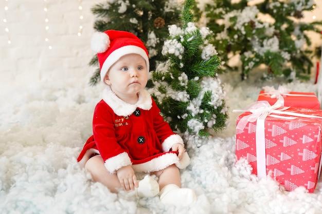 Baby im weihnachtsmannkostüm, das nahe weihnachtsbaum sitzt. familienurlaubskonzept. Premium Fotos