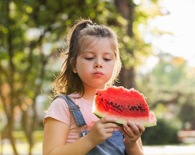 Baby in der natur, die eine wassermelonenscheibe hat Kostenlose Fotos