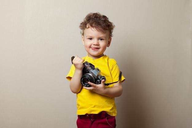 Baby in einem gelben t-shirt mit einer kamera in seinen händen. Premium Fotos