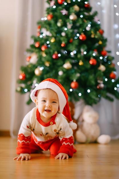Baby in einem gestrickten rentierkostüm und in der weihnachtsmannmütze kriecht vor einem weihnachtsbaum. hochwertiges foto Premium Fotos
