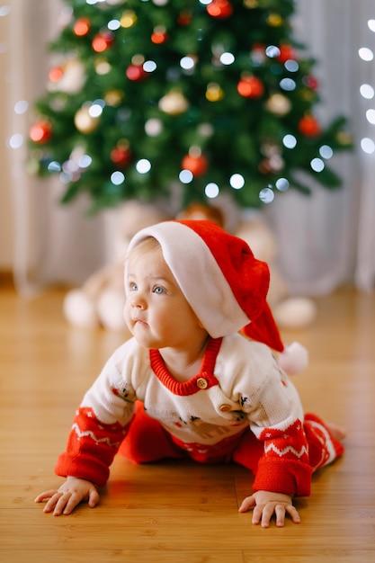 Baby in einem weihnachtskostüm und einer weihnachtsmütze kriecht vor einem weihnachtsbaum. hochwertiges foto Premium Fotos