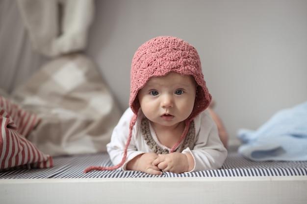 Baby in mütze in echtem kinderzimmer, sicherheit und pflege Premium Fotos