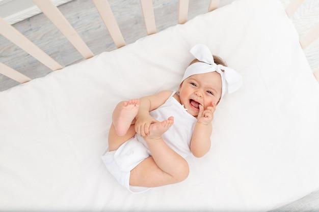 Baby in weißen kleidern, die in einer krippe liegen Premium Fotos