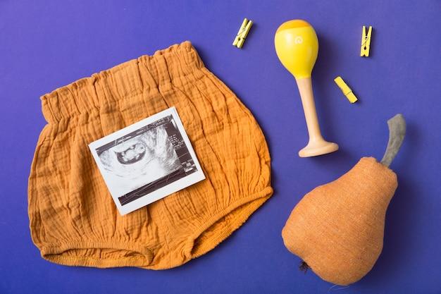 Baby ist kurz; gefüllte birne; geklapper und gelbe wäscheklammer auf blauem hintergrund Kostenlose Fotos