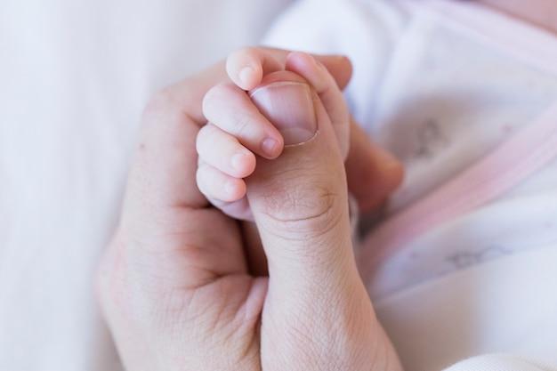 Baby kind, welches die hand des vaters, abschluss herauf ansichtliebe und familienkonzept hält Premium Fotos