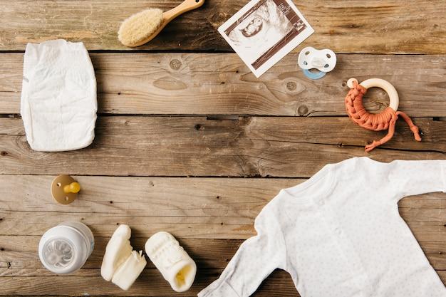 Baby kleidung; milchflasche; schnuller; bürste; windel und sonography bild auf holztisch Kostenlose Fotos
