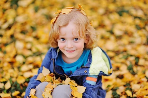 Baby - kleiner junge mit dem gelockten blonden haar lächelnd gegen gelben herbstlaub im park Premium Fotos