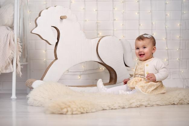 Baby mädchen sitzt in der nähe eines schaukelpferdes und einer mauer mit einer girlande aus glühbirnen Premium Fotos