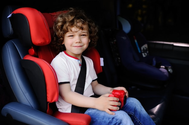 Baby mit dem gelockten haar, das in einem kinderautositz mit spielzeugauto in den händen sitzt Premium Fotos