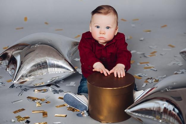 Baby mit goldener geschenkbox auf dem boden mit konfetti- und luftballonen. Premium Fotos